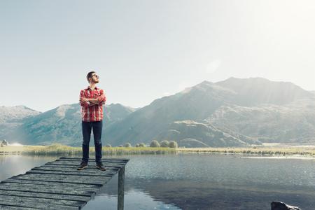 checked shirt: Man in checked shirt and eyeglasses on lake bank