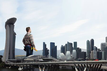 checked shirt: Builder man in checked shirt with tool belt on waist