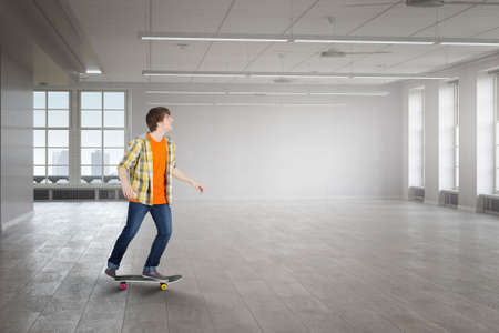 Teenager guy riding skateboard in building interior. Mixed media Stock Photo