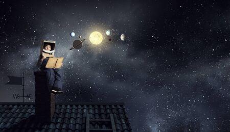 Muchacho divertido en el casco de cartón leyendo libro y un sueño que es astronauta