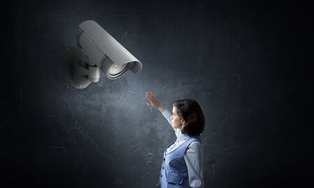keep an eye on: Unrecognizable businesswoman in room standing under security camera Stock Photo