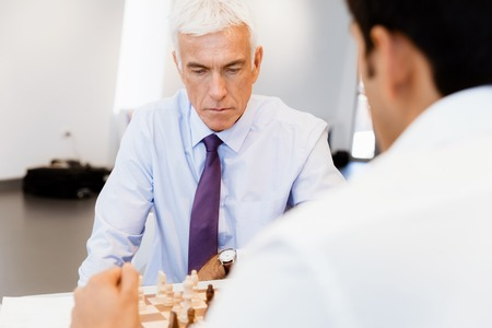 robustness: Two businessmen with chess in office