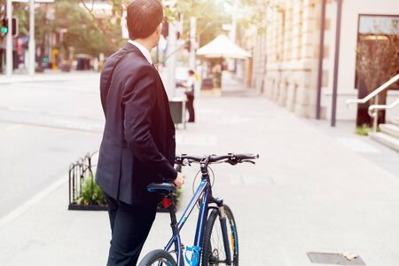 Young businessman wearing suit with bike outdoors Stock Photo