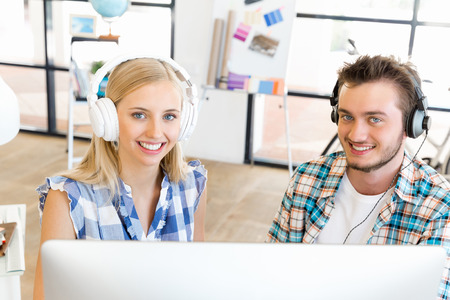 Two young office workers working together at the desk wearing headphones Stock Photo