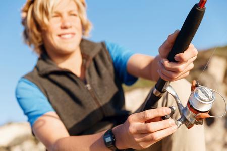 grandkid: Teenage boy fishing with rod at sea