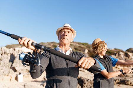 70s: Senior man fishing with his teenage grandson at seaside