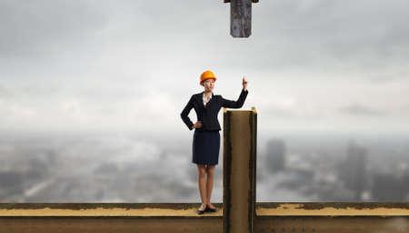 Attractive woman engineer inhardhat standing on balk