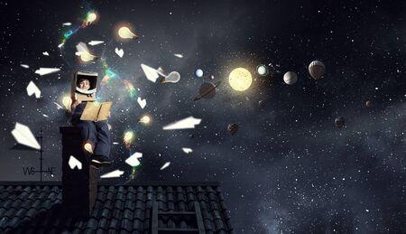 anochecer: Muchacho divertido en el casco de cartón leyendo libro y un sueño que es astronauta