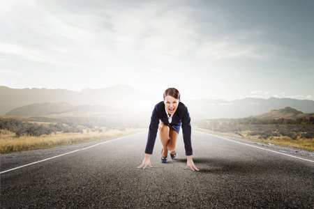 women sport: Young businesswoman in start pose on road ready to run Stock Photo