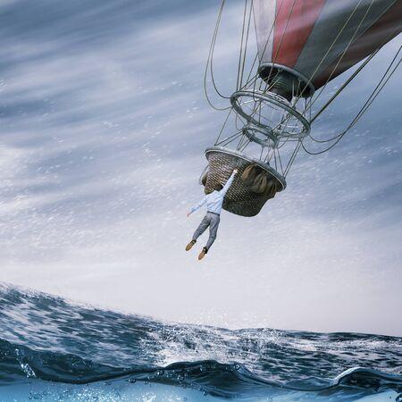 Businessman hanging on edge of aerostat high in sky Stock Photo