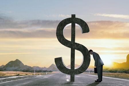 amanecer: Joven hombre de negocios con la maleta que se inclina la cabeza a gran signo de dólar