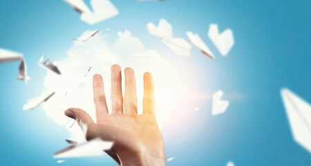 carelessness: Close view of female hand and many paper planes flying in air