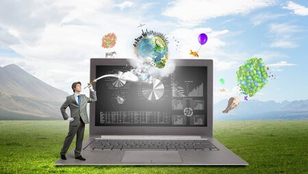 Magician with colorful balloons and big laptop. Elements of this image are furnished by NASA