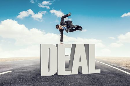 handstand: Active businessman making handstand on word deal