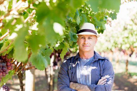 Man wearing hat standing in vineyard