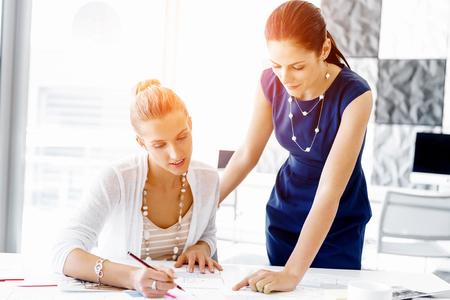사무실에서 함께 작동하는 두 여성 동료 스톡 콘텐츠