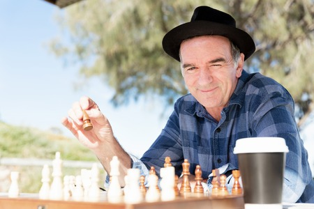 pawn adult: Elderly man sitting outdoors with chess