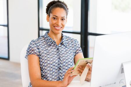 Portrait of beautiful smiling afro-american office worker sitting in office and holding photo frame