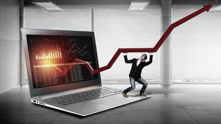 average guy: Young man on huge laptop making red arrow graph grow. Mixed media