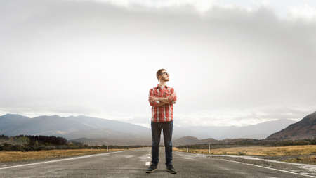 checked: Pensive young man in checked shirt standing on road Stock Photo
