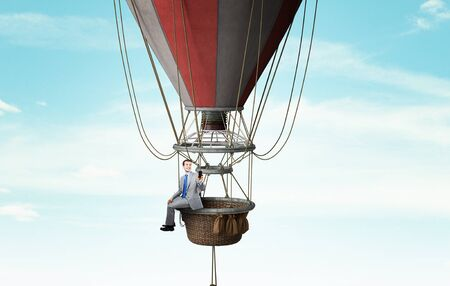 fun at work: Businessman flying in aerostat high in sky Stock Photo