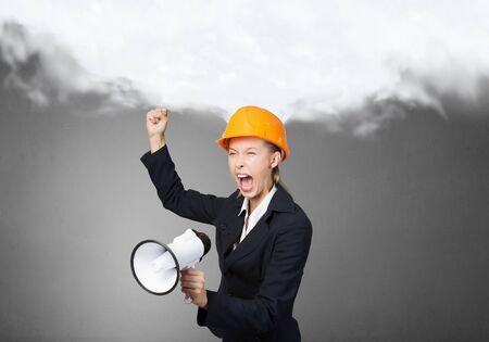 woman engineer: Emotional woman engineer in helmet screaming in megaphone