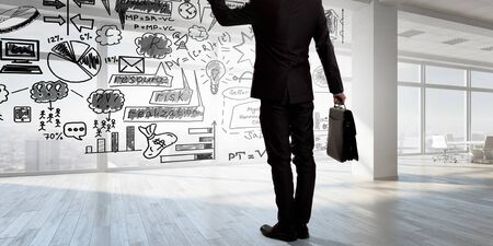 market bottom: Bottom view of businessman and business ideas sketched at background. Mixed media Stock Photo