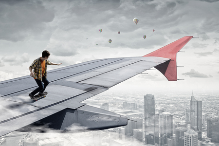 Teenager guy riding skateboard on airplane wing