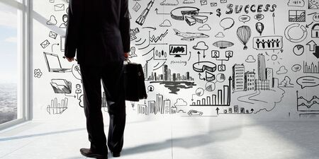 market bottom: Bottom view of businessman and business ideas sketched at background. mixed Stock Photo