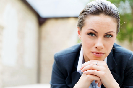 thirties: Portrait of young business woman outdoors sitting and thinking