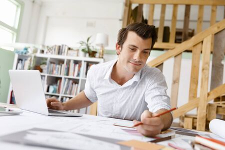 Male architect with computer studying plans in office Stock Photo