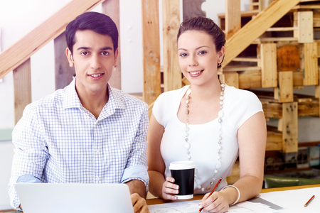 Two young architects in casual clothes in an office working with drafts