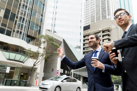 catching taxi: Two young businessmen in suits catching taxi