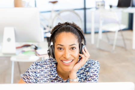 Portrait of beautiful smiling afro-american office worker sitting in office with headphones