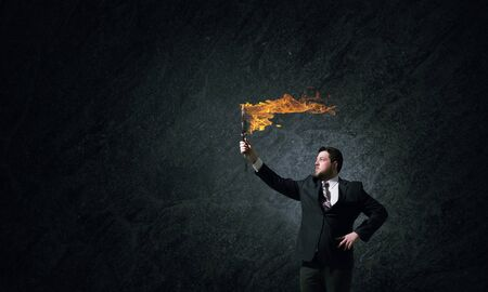 burning money: Young businessman in darkness holding burning torch in hand Stock Photo
