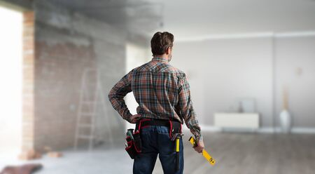Builder man in checked shirt with tool belt on waist. Mixed media