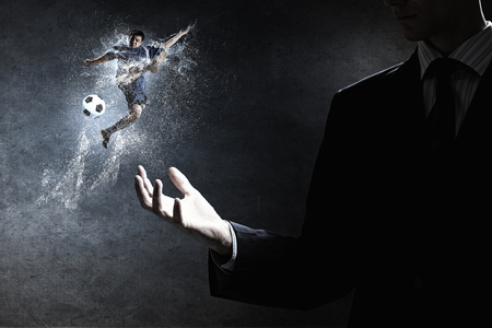 gamblers: Hand of businessman holding in palm football game player