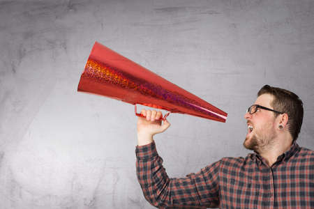 Guy in checked shirt make announcement in red paper trumpet