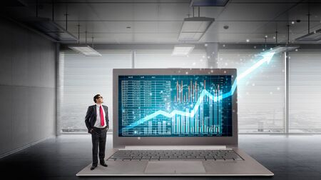 average guy: Adult businessman standing on huge laptop and graphs and diagrams on screen. Mixed media Stock Photo