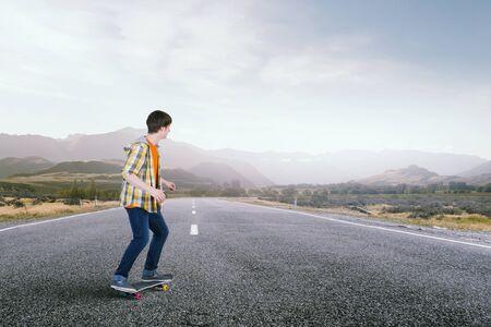 skateboarder: Teenager guy riding skateboard on asphalt road