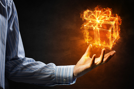 Glowing fire gift box icon on male palm Stock Photo