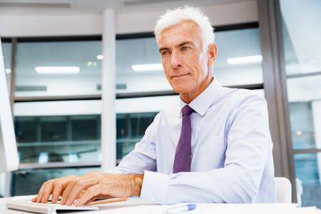 working on computer: Businessman sitting in office working with computer Stock Photo