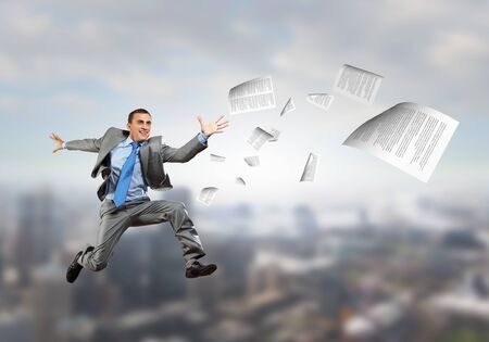 Young cheerful businessman jumping high presenting success concept