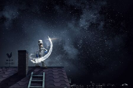 anochecer: Funny girl in space costume on house roof dreaming she is astronaut Foto de archivo