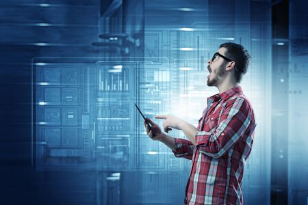 checked shirt: Young man in checked shirt reading on tablet Stock Photo
