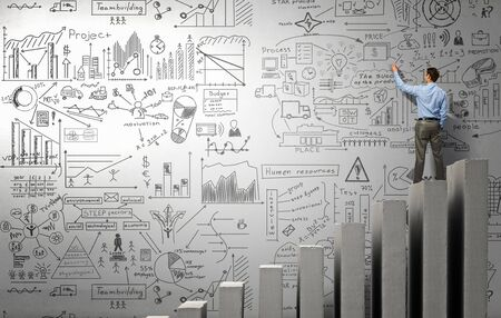 Businessman drawing business success plan and strategy on wall in room