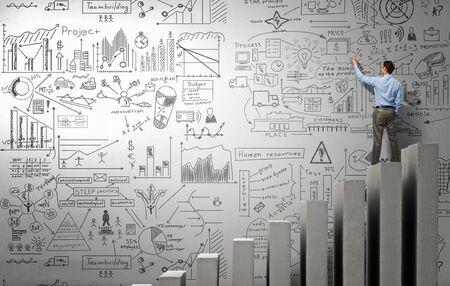 Homme d'affaires de dessin plan et une stratégie de réussite de l'entreprise sur le mur dans la chambre
