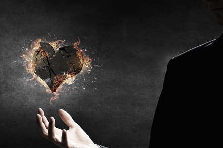 hands fire passion: Stone heart in fire flames in businessman palm