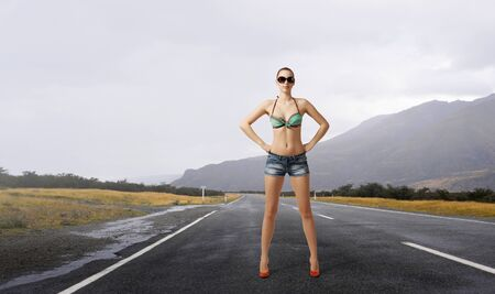 Young attractive girl in bikini and shorts on road