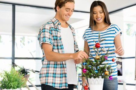 decorating christmas tree: Young people in casual clothes decorating christmas tree in office